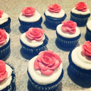 Chocolate cupcakes with buttercream frosting and a coral buttercream rose